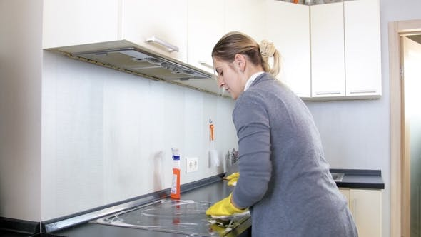 Thumbnail for Video of Housewife in Rubber Gloves Spraying Detergent Over Electric Hob and Washing It with Sponge