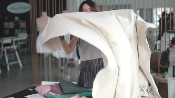 Thumbnail for Young Asian Woman Working in a Sewing Studio. Girl Designer Clothes Scraps Cloth on the Table