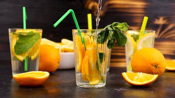 Pouring Water in a Glass with Slices of Oranges