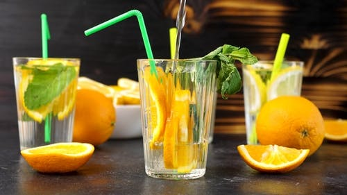 Pouring Water in a Glass with Fresh Cutted Slices of Oranges