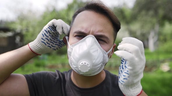 Thumbnail for Man in Working Gloves Puts on the Resperator in  Outdoors, Respiratory Protection for Human, Securit