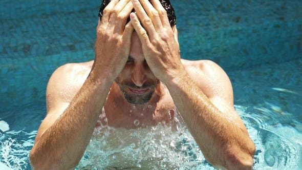 Man Wetting Hair in Pool
