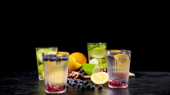 Thumbnail for Different Organic Fruits next to Four Glasses of Detox Water