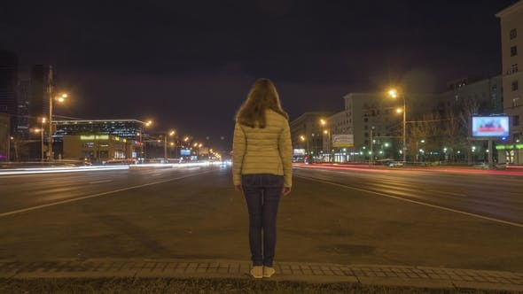 Cover Image for Woman Standing Still and Traffic of Cars on Highway at Night in the Illuminated City