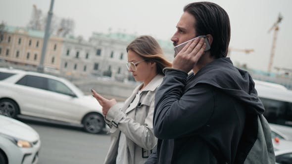 Thumbnail for Couple of Tourists Walking in a City Street with Phone Use Navigation Applications, Man and Woman