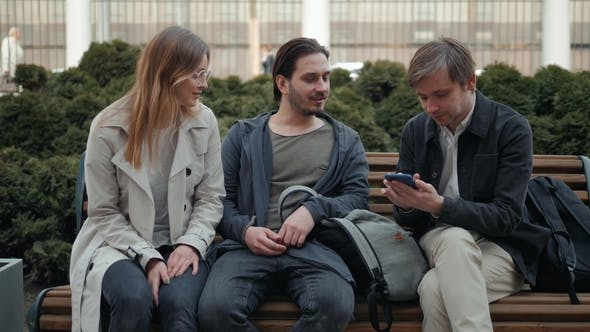 Thumbnail for Three Amazed Students Checking on Line Content on a Smart Phone in the Street, Happy Friends on City
