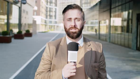 Male TV Reporter with Mic Talking at Camera Outdoors