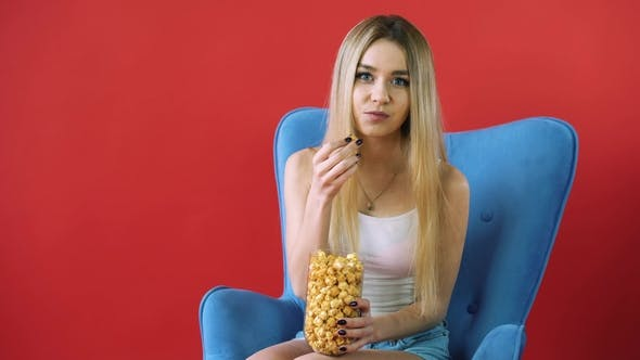 Thumbnail for Pretty Young Woman Sitting on a Sofa with Her Legs Crossed, Eating Popcorn and Watching TV.