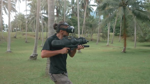 Man in Virtual Reality Headset with Weapon in the Jungle Running