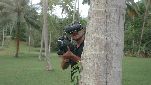 Thumbnail for Man with Weapon Playing Virtual Reality Game in the Jungle