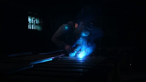 Cover Image for Welder Works in a Mask while Sparks Fly in Different Directions