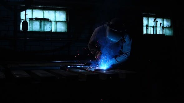 Thumbnail for Welder Works in a Mask while Sparks Fly in Different Directions