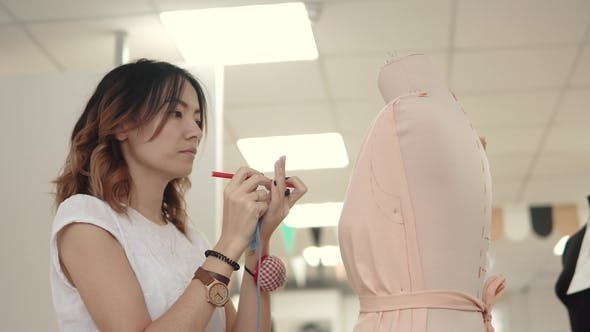 Thumbnail for Seamstress Creates a Model of Clothes on the Mannequin. Asian Girl Designer Clothes