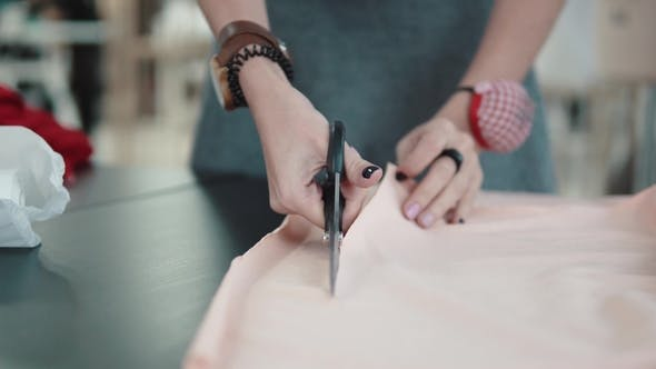 Thumbnail for Woman Cuts Fabric with Scissors for Cutting