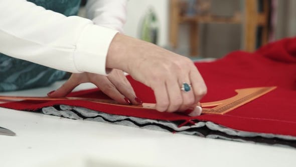 Thumbnail for Woman Is Applying a Pattern on the Fabric. the Designer of Clothes Draws Chalk on a Red Cloth