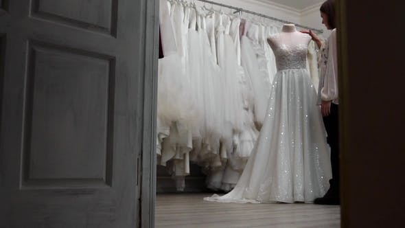 Thumbnail for Beautiful Girl Looking at Wedding Dress in the Shop Compared to Other Dresses