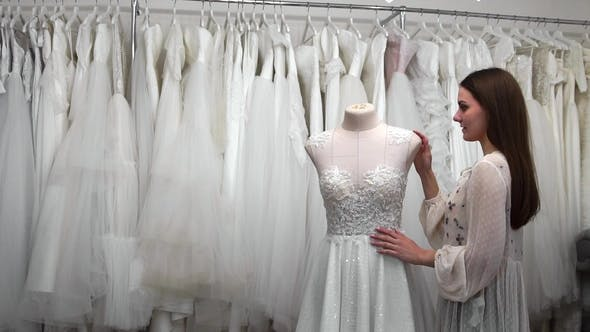 Cover Image for Beautiful Girl Looking at Wedding Dress in the Shop Compared to Other Dresses