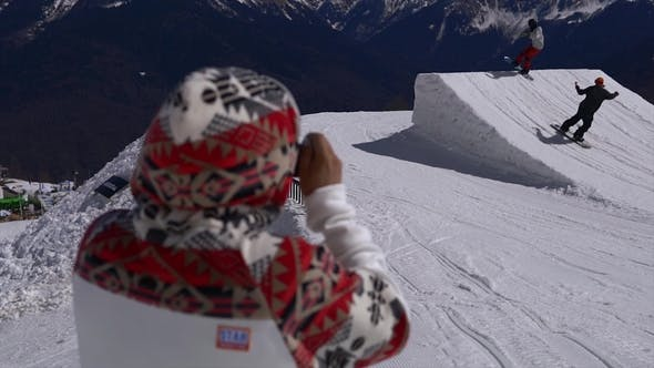 Thumbnail for Man Filming Snowboarders with Action Camera