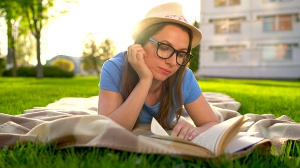 Thumbnail for Girl in Glasses Reading Book Lying Down on a Blanket in the Park at Sunset