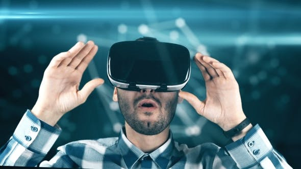 A Young Man with a Beard in Glasses of Virtual Reality on a Technological Background