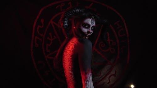 démoniaque avec gros cornes plie son dos contre l'arrière-plan du pentagramme