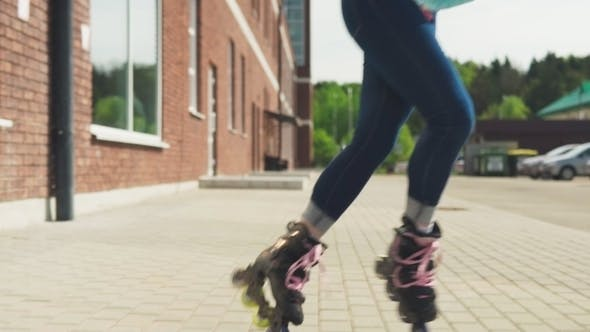 Young Woman Eenjoys Rollerblading on a City Street