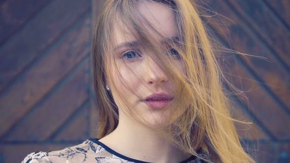 Thumbnail for Girl with Long Wheat-colored Hair. Looks Directly Into the Camera, the Hair Develops the Wind