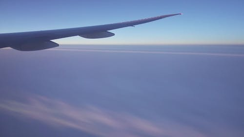 Looking on Wing and Fumes of Flying Airplane