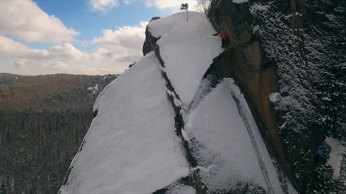 Aerial View of a Rock Climber Climbing a Steep Cliffs During a Sunny Winter Day