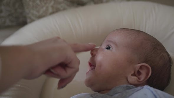 Thumbnail for Mother Touches Little Son's Nose Who Lying in His Crib. Charming Baby Smile