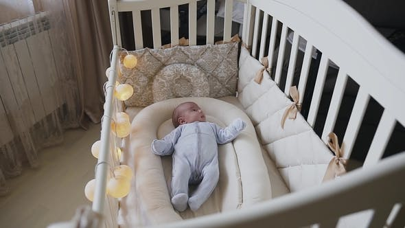 Thumbnail for A Newborn Baby Boy in a Crib in the Bedroom Is Trying To Fall Asleep. Cute 3 Months Old Baby Lying