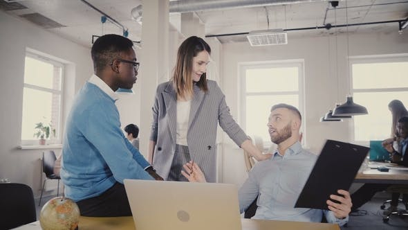 Thumbnail for Beautiful Female CEO Discussing Work Process with Young Multiethnic Colleagues, Looks at Laptop
