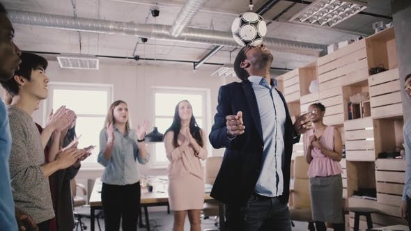 Thumbnail for Happy African American Boss Juggles Ball on Head. Multiethnic Business People Celebrate Success in