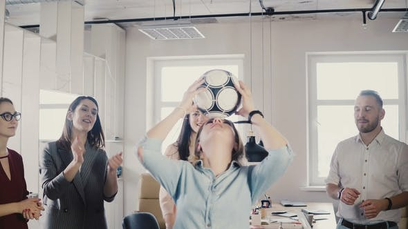 Thumbnail for Caucasian Girl Juggles Football on Head in Office. Happy Multiracial Business People Celebrate Work