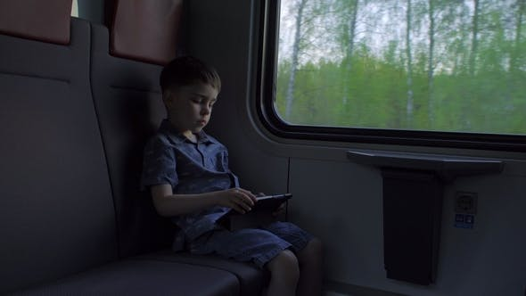 Thumbnail for The Boy Is Riding in the Train, Playing Games on the Tablet
