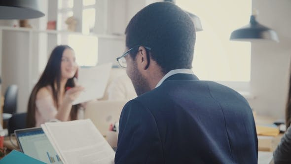 Thumbnail for African American Businessman Reading Through Documents at Multiethnic Office Meeting