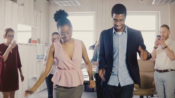 Счастливые афро-американские друзья, которые танцуют в офисе партии
