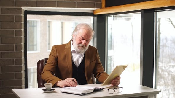 Thumbnail for Handsome Mature Businessman in Classic Suit and Eyeglasses Working in His Office.