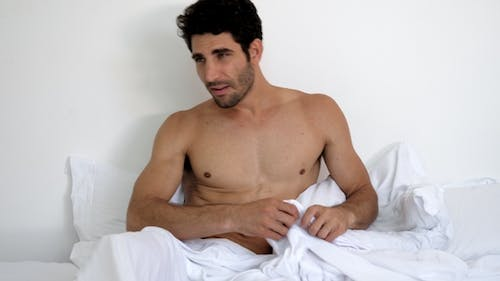 Man Dressing in Bed