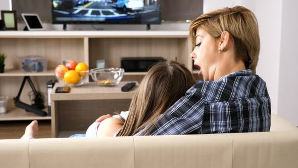 Thumbnail for Mother Is Embracing Her Daughter While Looking at TV