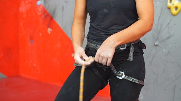 Thumbnail for Caucasian Woman Putting on Belaying Harness for Practice on Artificial Rock Wall.