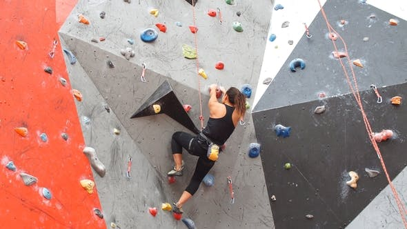 Thumbnail for Portrait of Woman on Artificial Exercise Climbing Wall.