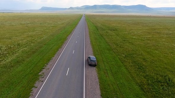 Thumbnail for Aerial View of the Endless Fields, Hills, Haystacks, Road and Car in Motion