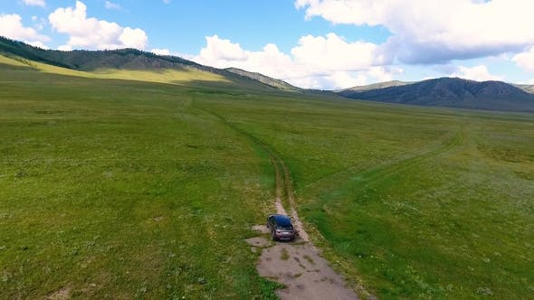 Thumbnail for A View From the Air To Green Meadows, Hills in the Distance and a Car Riding Off-road