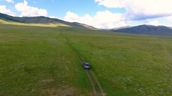 Thumbnail for Aerial View of Green Meadows, Hills in the Distance and a Car Riding Off-road