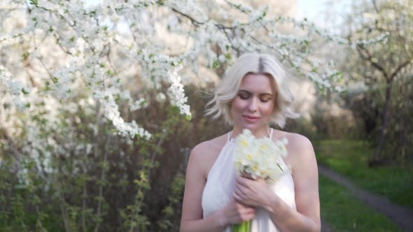 Thumbnail for Blonde Girl Walking on a Blooming Garden and Resting