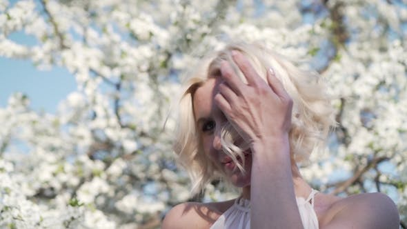 Thumbnail for Adorable Young Blonde Girl with Make-up Is Lovely Smiling and Smelling the White Flower in the