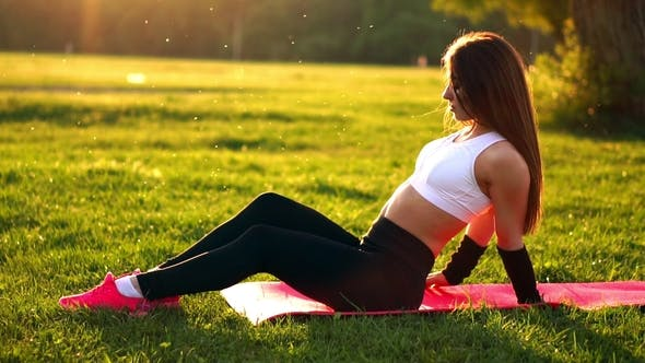 Thumbnail for Young and Beautiful Woman Is Sitting on the Mat During Break in Her Fitness Workout