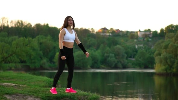 Cover Image for Sporty Brunette in a White Top and Black Tight Pants and Pink Sneakers in the Sunlight Stretches