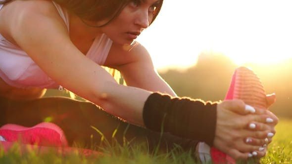 Thumbnail for Sexy Sporty Brunette Girl in Pink Shoes at Sunset in a Park Stretches